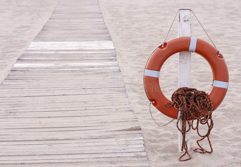 Bouée de sauvetage à côté de promenade sur la plage photo stock
