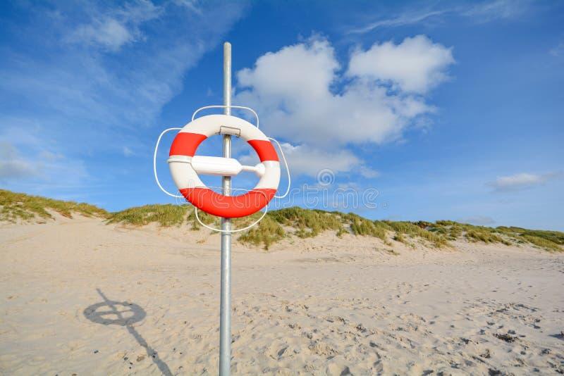 Bouée de sauvetage aux dunes de plage et de sable près de Blavand, Jutland Danemark image stock