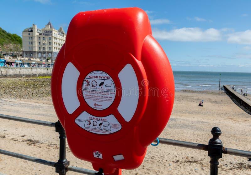 Bouée de sauvetage avec les signes bilingues plage Llandudno le Pays de Galles en mai 2019 du nord images libres de droits