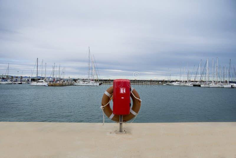 Bouée de sauvetage dans la marina pour des yachts Cercle rouge sur le dock de bateau yachts et bateaux uxury en Valencia Port At  photo libre de droits