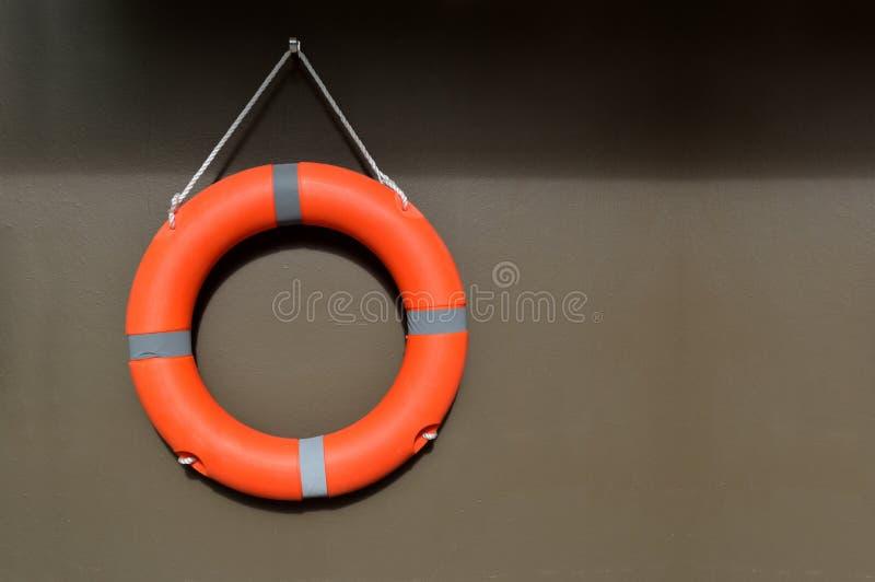 Bouée de sauvetage orange accrochant sur un mur photographie stock
