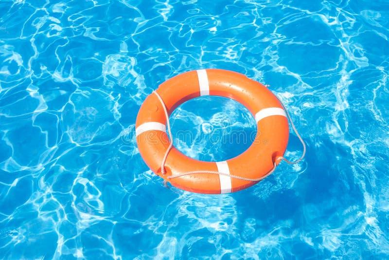 Bouée de sauvetage orange sur un fond de piscine d'eau bleue images libres de droits