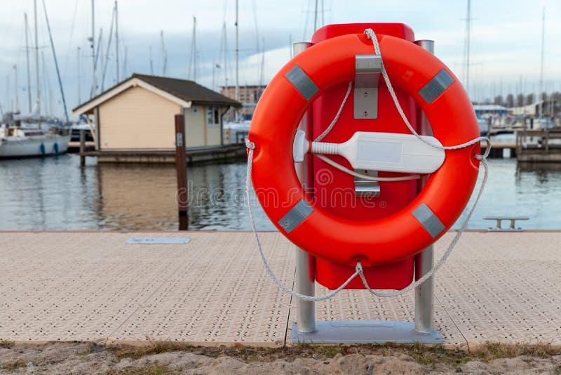 Bouée de sauvetage rouge placée sur une côte de lac images stock