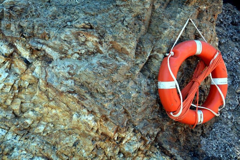 Bouée de sauvetage sur la plage de roche photographie stock libre de droits