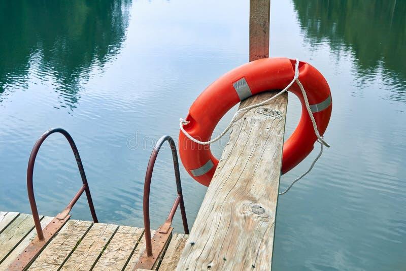 Bouée de sauvetage sur un pilier d'un lac de forêt un jour nuageux en été photographie stock