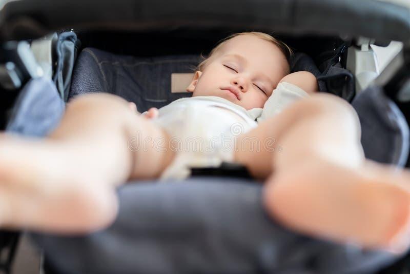 Bou louro caucasiano adorável bonito da criança que dorme no carrinho de criança no dia Cuidados médicos das crianças e conceito  fotografia de stock royalty free