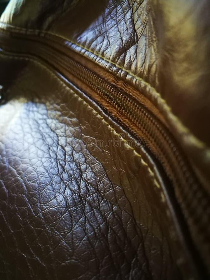 Bouche brune foncée de sac en cuir de modèle de fond avec la fermeture de tirette Points entre la tirette et le sac en cuir photographie stock