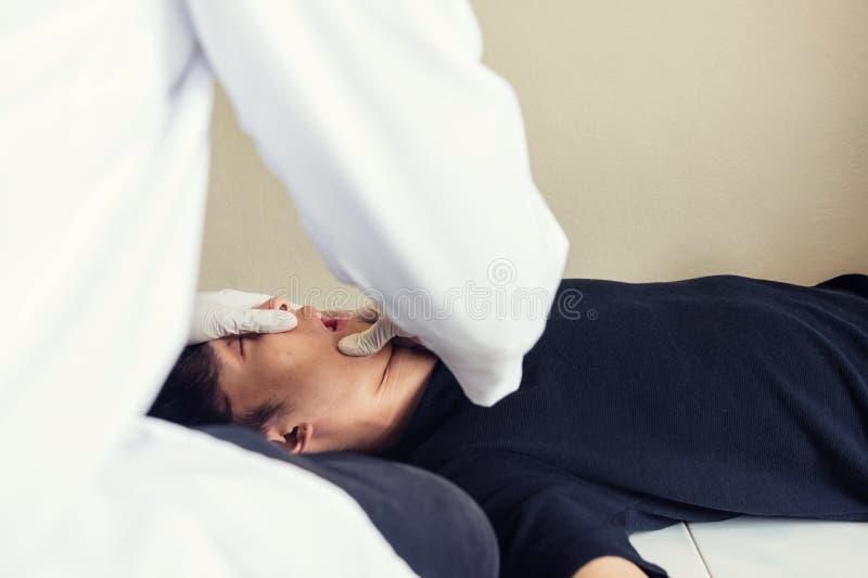 Bouche dépendante ouverte d'homme de docteur pour vérifier des pilules images stock