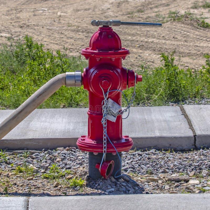 Bouche d'incendie avec un tuyau et une clé apposés images libres de droits