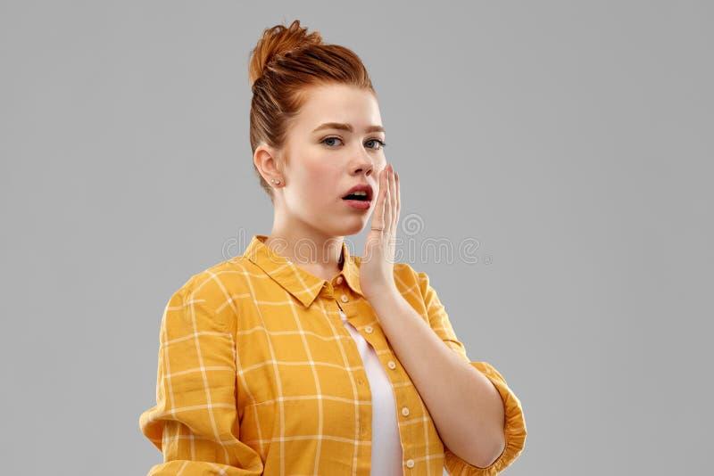 Bouche d'une chevelure rouge de b?che d'adolescente ? la main photographie stock