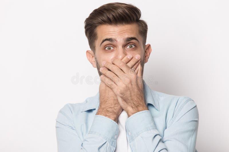 Bouche horrifiée de bâche d'homme avec des mains regardant la caméra photos stock