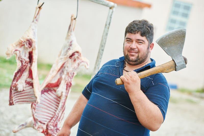 Boucher avec de la viande de carcasse de hache et de moutons image stock
