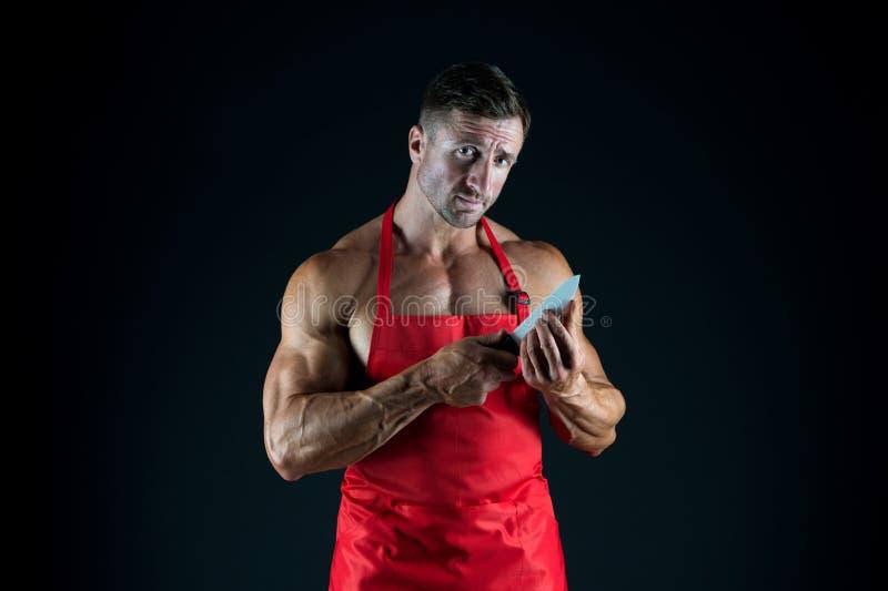 Boucher avec le couteau homme avec le torse musculaire dans le tablier de chef cuisine Femme au foyer masculine mari dans la cuis photos stock