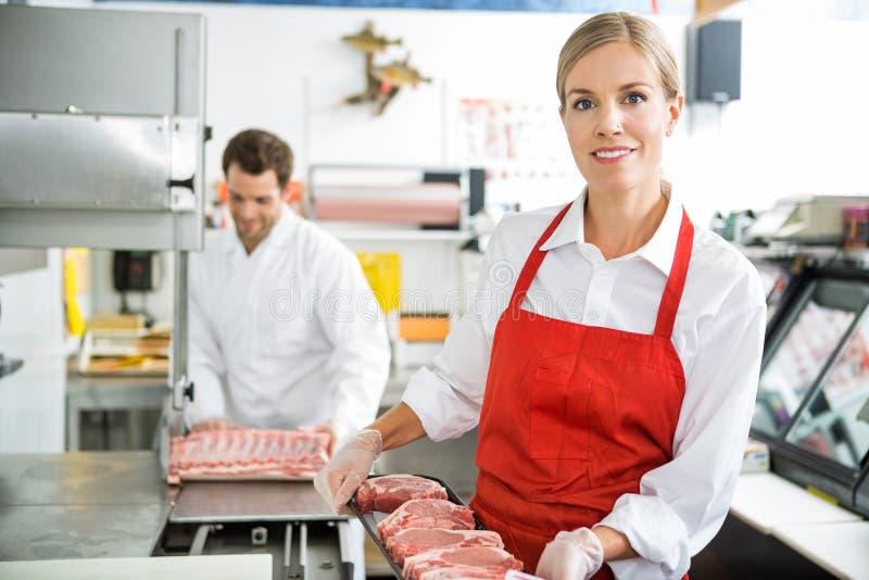 Boucher de sourire Holding Meat Tray At Store photographie stock libre de droits