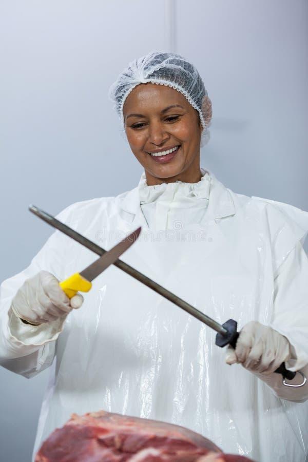 Boucher féminin affilant son couteau photos stock