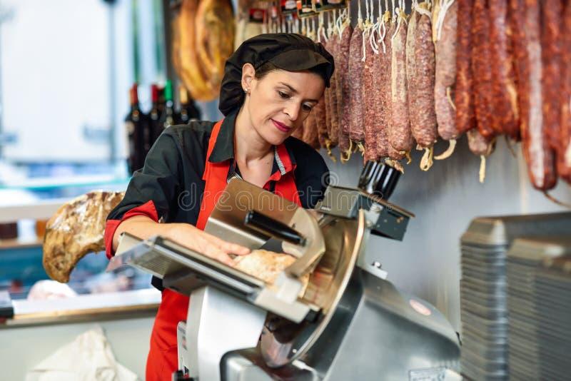 Boucher féminin coupant le jambon de York dans une découpeuse photos libres de droits