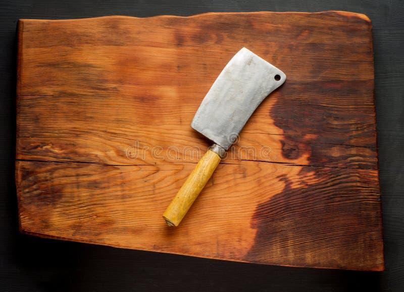 boucher Les fendoirs de viande de boucherie de vintage sur la cuisine en bois foncée embarquent le fond image libre de droits