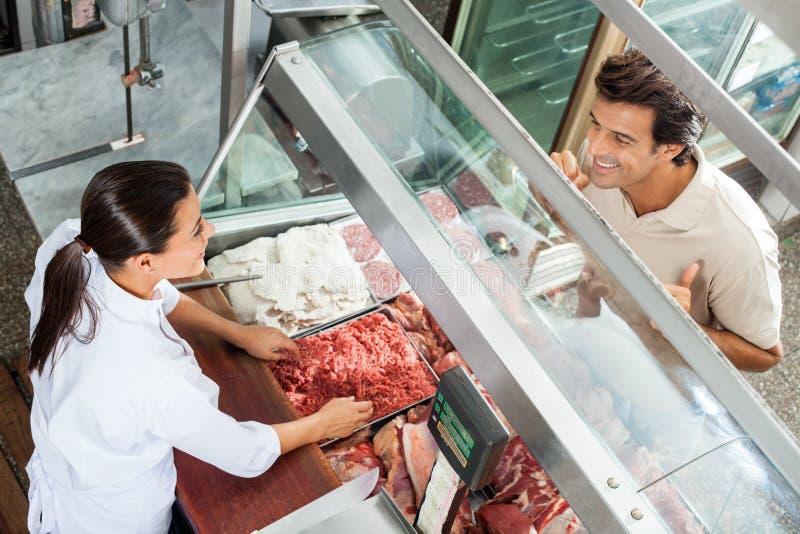 Boucher Selling Minced Meat au client masculin photographie stock libre de droits