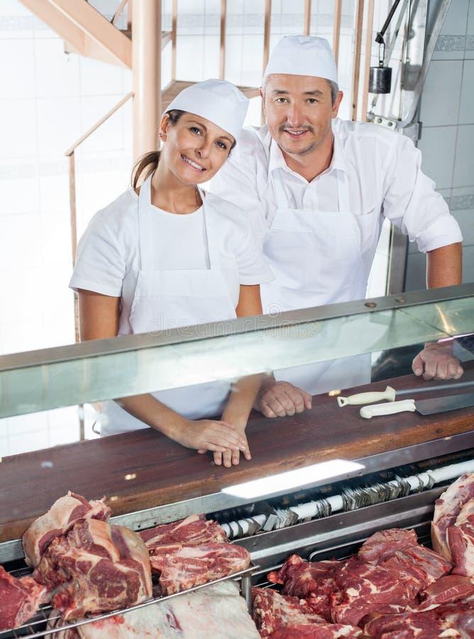 Bouchers amicaux se tenant au compteur de viande photo stock