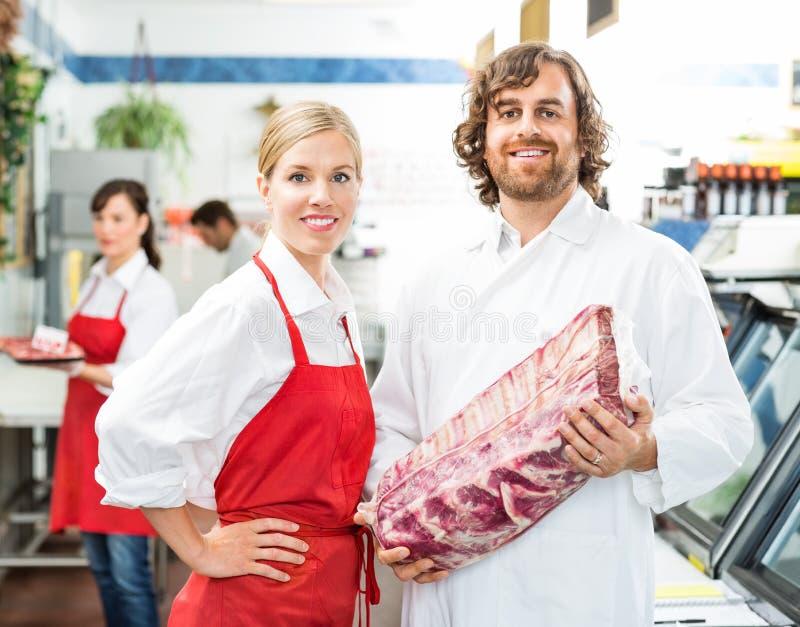 Bouchers sûrs avec le paquet de viande photos stock
