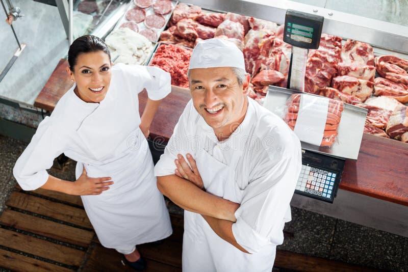 Bouchers sûrs se tenant au compteur de boucherie image stock