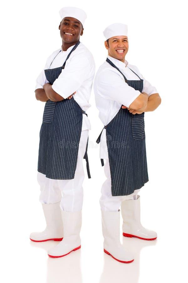 Bouchers se tenant de nouveau au dos images stock