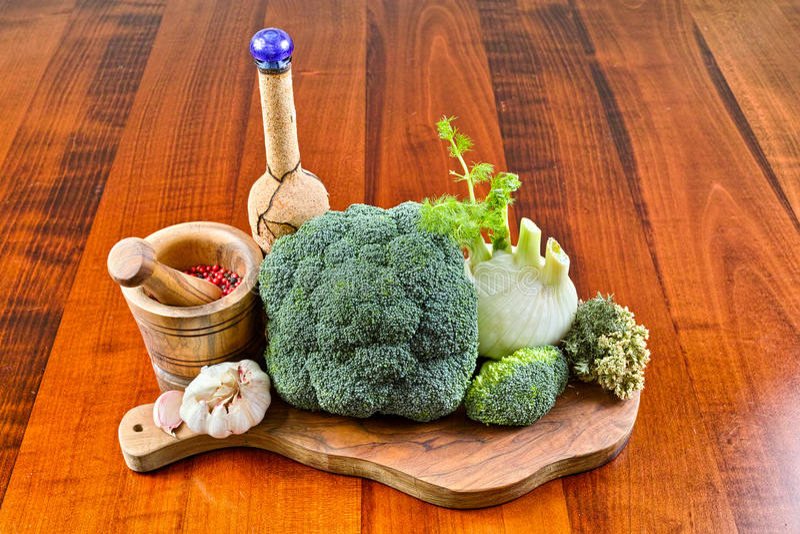 Bouchez la bouteille, mortier en bois olive, légumes verts, brocoli, fenouil, ail photos stock