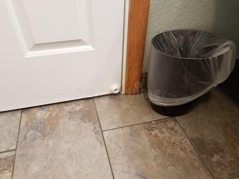 Bouchon blanc de porte avec le carrelage et la poubelle bruns images stock