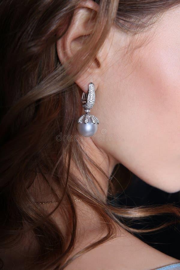 Boucle d'oreille avec des perles et des diamants dans l'oreille du ` s de fille image libre de droits