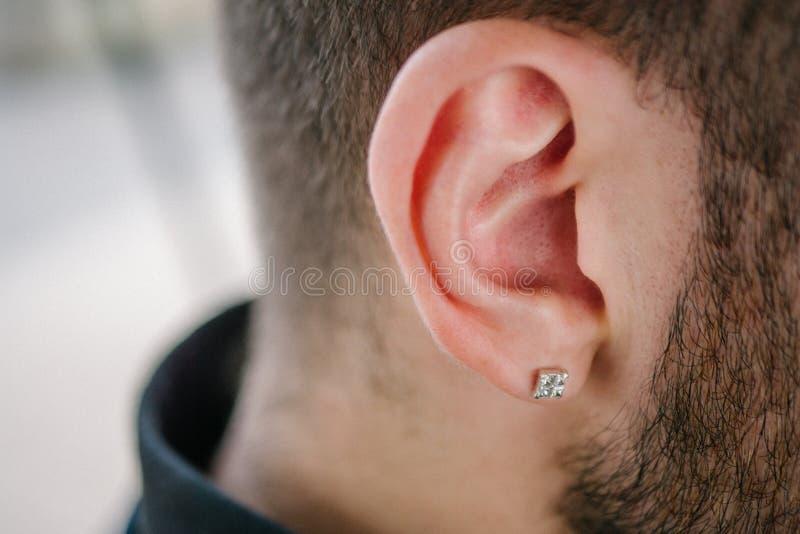 Boucle d'oreille dans l'oreille masculine Partie perçante du corps photos stock