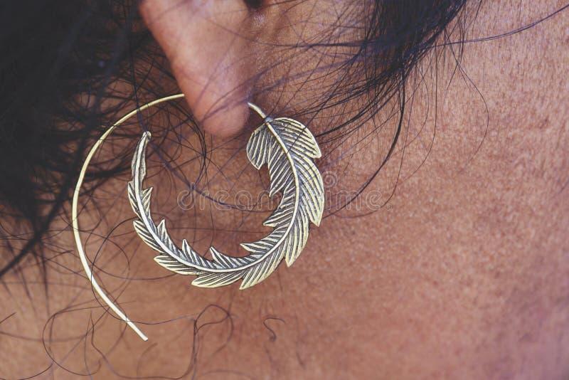 Boucle d'oreille en laiton de port d'oreille masculine dans la forme de la feuille photos stock