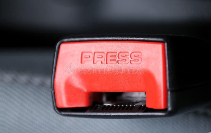 Boucle de ceinture de sécurité avec l'orientation sur l'inscription de PRESSE image stock