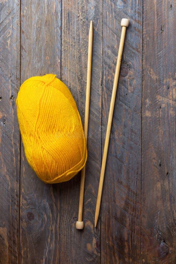 Boucle des aiguilles de tricotage jaunes de fil de laine sur le fond âgé en bois de planche Vêtements de passe-temps de métiers f image libre de droits