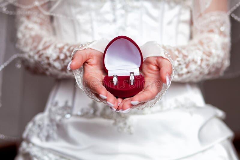 Boucles avec le cadre dans des mains de jeune mariée photos libres de droits