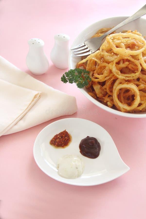 Boucles d'oignon et condiments photos stock
