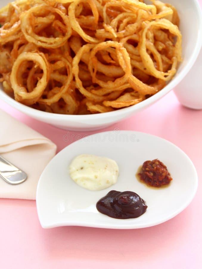 Boucles d'oignon et condiments photos libres de droits