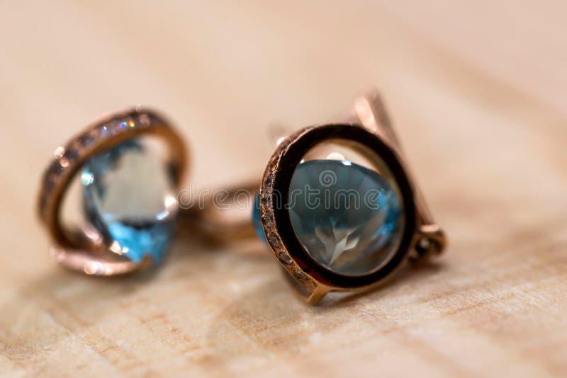 Boucles d'oreille d'or avec les cristaux bleus clairs image libre de droits