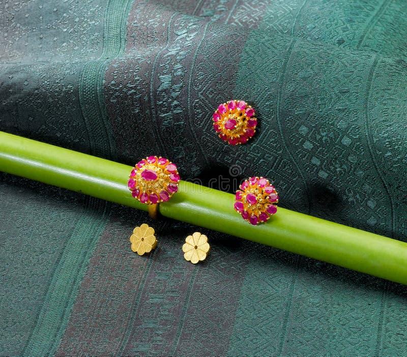 Boucles d'oreille d'or et boucle décorées par des pierres gemmes photo libre de droits