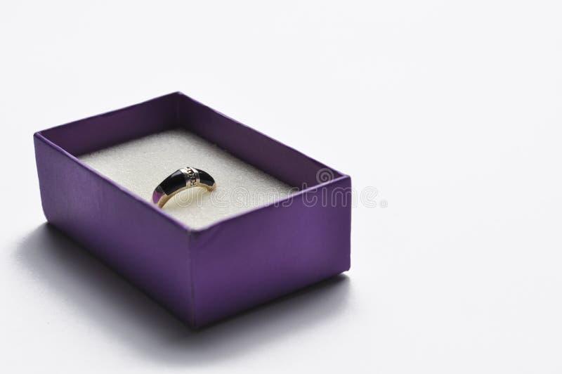 Boucles d'oreille dans une bo?te pourpre d'isolement sur un fond blanc Copiez l'espace photos libres de droits