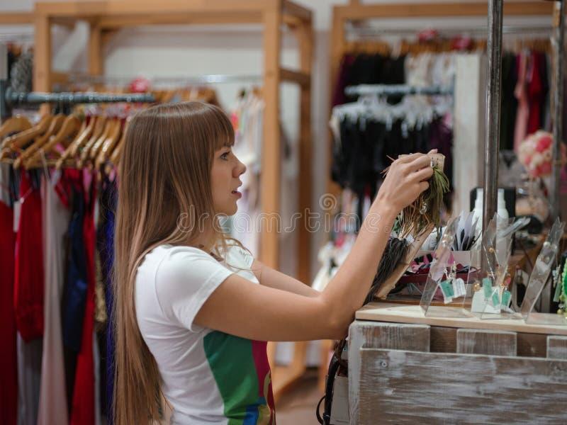 Boucles d'oreille de achat de jeune fille sur un fond de boutique Supports avec des accessoires, des vêtements et des bijoux Conc photographie stock