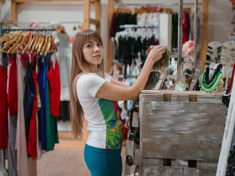 Boucles d'oreille de achat de jeune fille sur un fond de boutique Supports avec des accessoires, des vêtements et des bijoux Conc image libre de droits