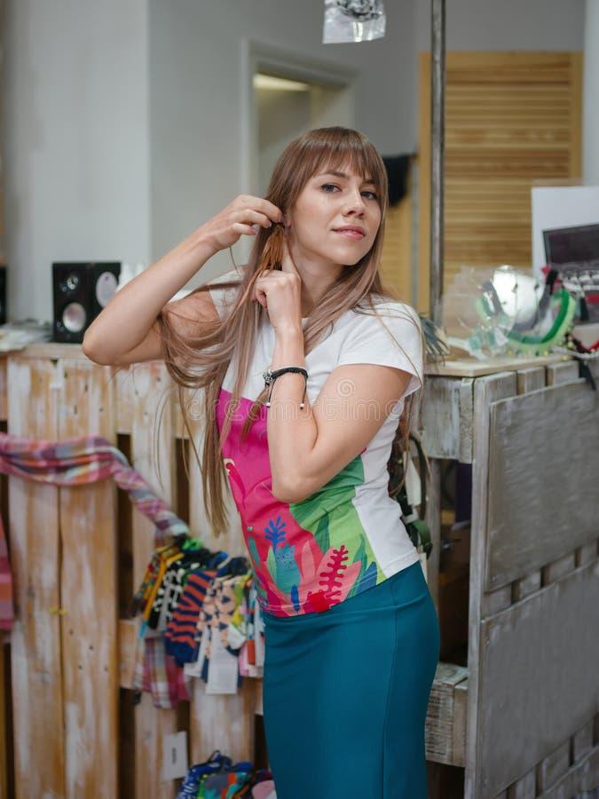 Boucles d'oreille de achat de jeune fille sur un fond de boutique Supports avec des accessoires, des vêtements et des bijoux Conc images stock
