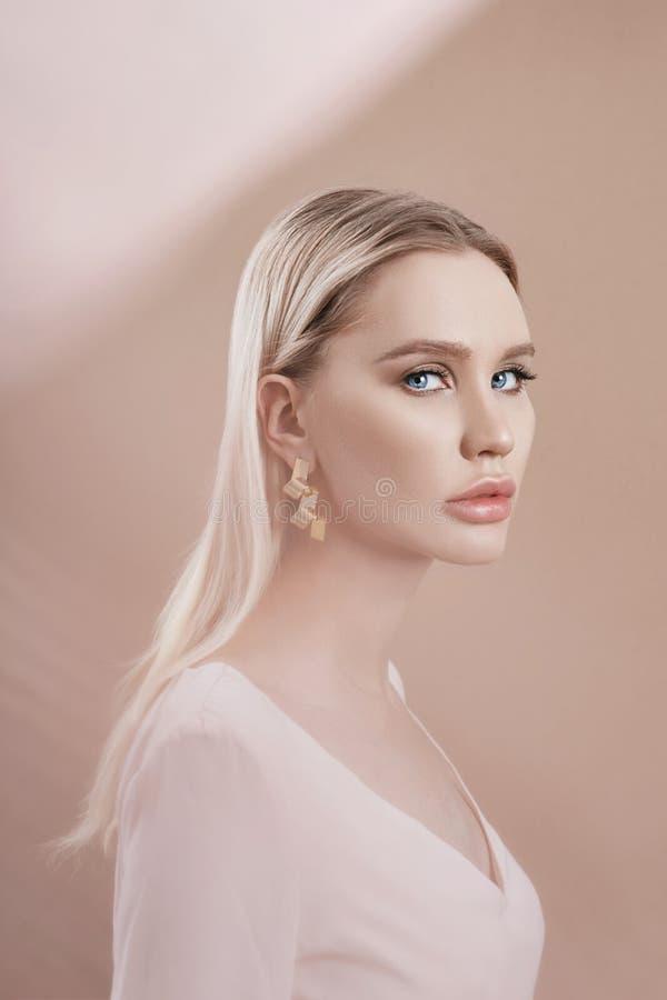 Boucles d'oreille et bijoux dans l'oreille d'une femme blonde sexy par un tissu coloré transparent Fille blonde parfaite, mystéri photos stock