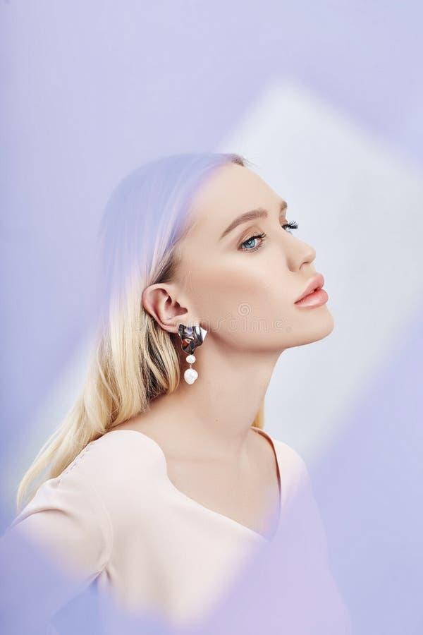 Boucles d'oreille et bijoux dans l'oreille d'une femme blonde sexy par un tissu coloré transparent Fille blonde parfaite, mystéri image libre de droits