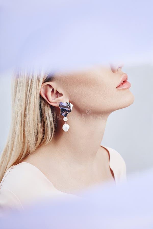 Boucles d'oreille et bijoux dans l'oreille d'une femme blonde sexy par un tissu coloré transparent Fille blonde parfaite, mystéri photo stock