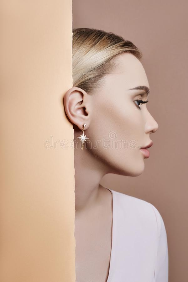 Boucles d'oreille et bijoux dans l'oreille d'une femme blonde sexy pressée contre le beige de papier Fille blonde parfaite, regar photo libre de droits