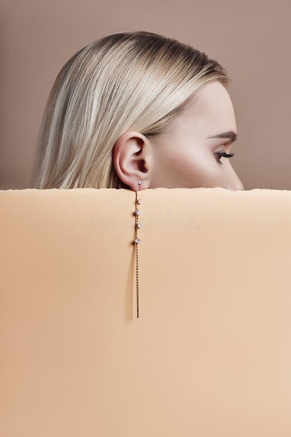 Boucles d'oreille et bijoux dans l'oreille d'une femme blonde sexy pressée contre le beige de papier Fille blonde parfaite, regar image stock
