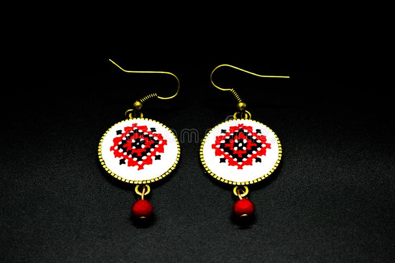 Boucles d'oreille faites main avec le modèle traditionnel roumain rouge et noir D'isolement sur le noir photos stock