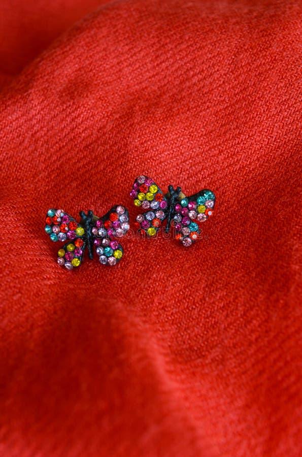 Boucles d'oreille faites main colorées, d'isolement sur le fond rouge de tissu photos libres de droits