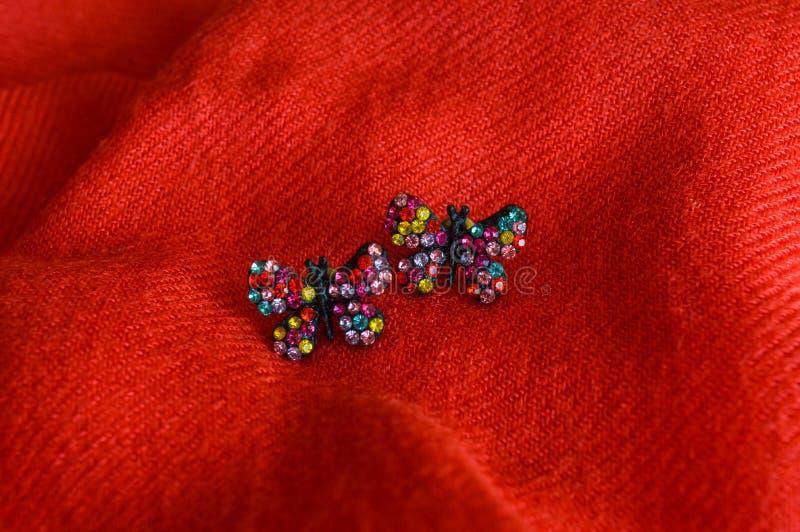 Boucles d'oreille faites main colorées, sur le fond rouge de tissu photographie stock libre de droits
